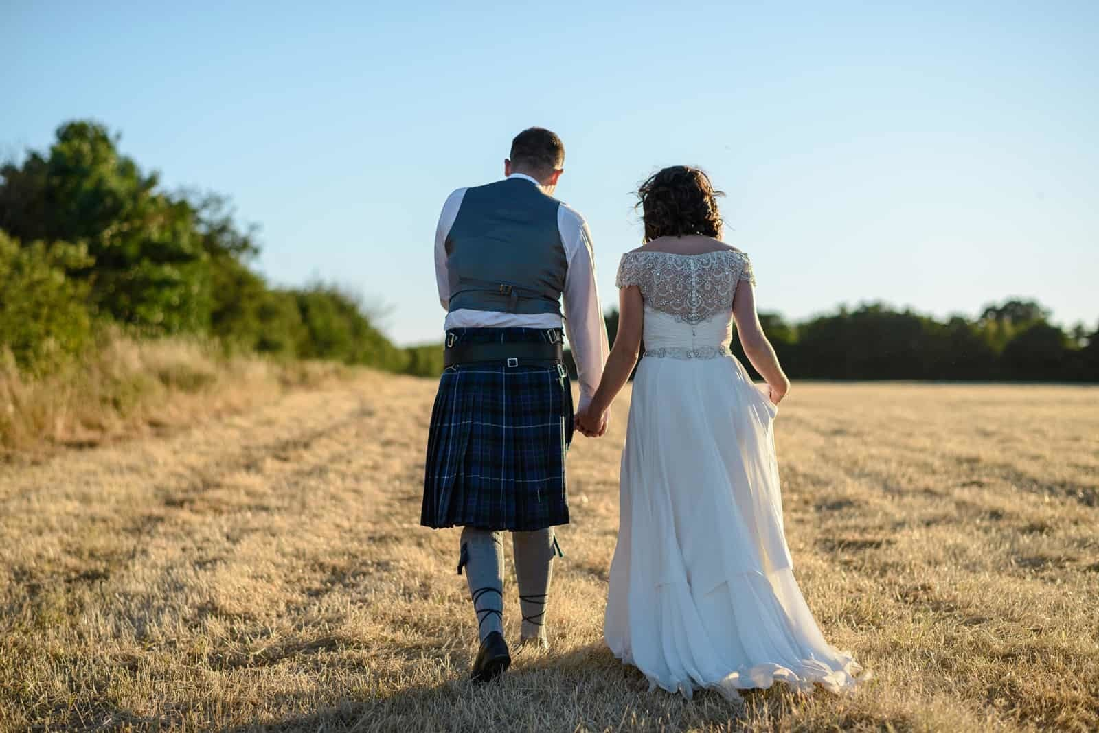 Andy Dane Photography - bride and groom walking through field